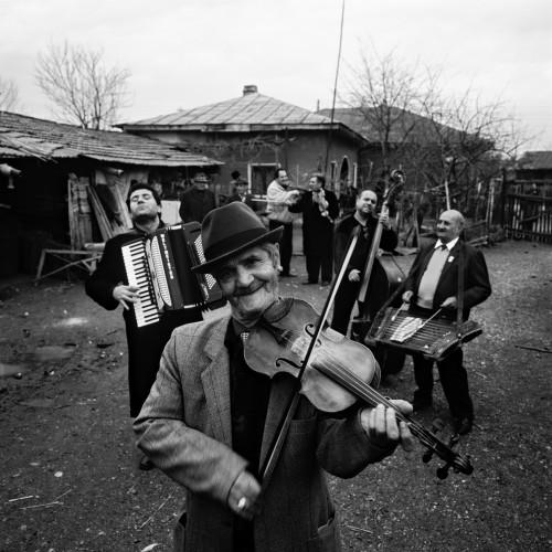 ルーマニアのクレジャニ村で、〇〇年一二月二六日に撮影したタラフ・ドゥ・ハイドゥークス。一番前でヴァイオリンを弾いているのは、今は亡きニコラエ爺さん。〈独裁者のバラード(Balada Conducatorolui)〉という曲で「(チャウシェスクが失脚した八九年一二月)二二日という日に生きた時間が戻ってきた」と歌った。